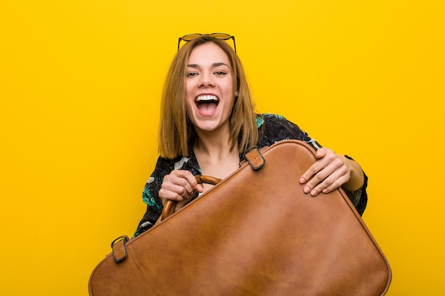 Young woman ready to go to vacation over yellow