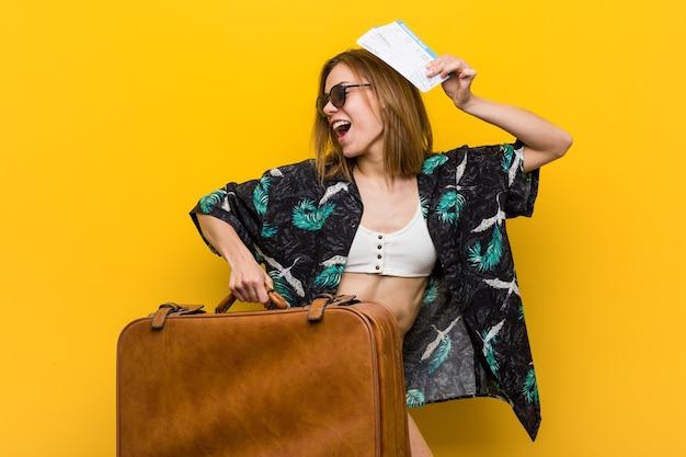 黄色の背景で休暇に行く準備ができて若い女性