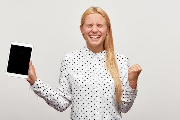 Молодая женщина, готовая прыгнуть от счастья, сжала кулак от радости, выглядит довольной, радуется с планшетом в руке