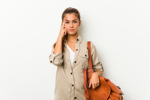 Young woman ready for a travel pointing temple with finger, thinking, focused on a task