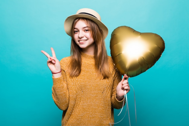 Young woman receives air baloon on anniversary celebration isolated over color wall