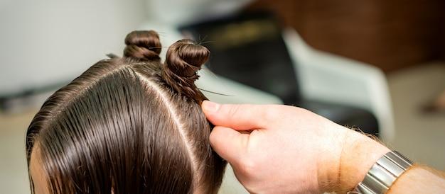Молодая женщина получает процесс прически парикмахером в салоне красоты