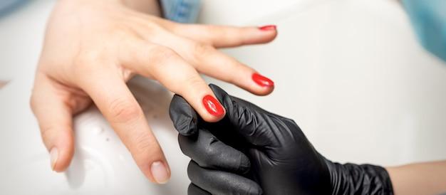 若い女性はネイルサロンでプロのマニキュアマスターによって赤いマニキュアを受け取ります