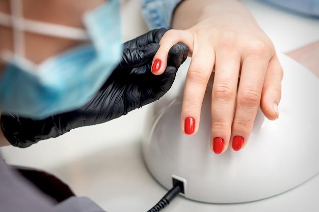 Молодая женщина получает красный лак для ногтей