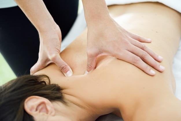 Молодая женщина получает массаж спины в спа-центре.