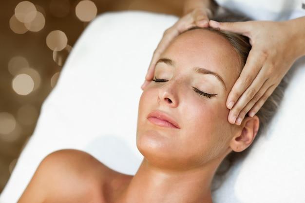 Молодая женщина получает массаж головы в спа-центре.