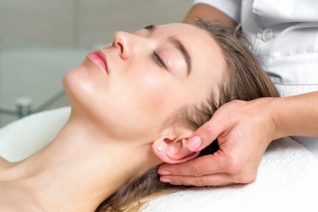 Молодая женщина получает массаж головы.