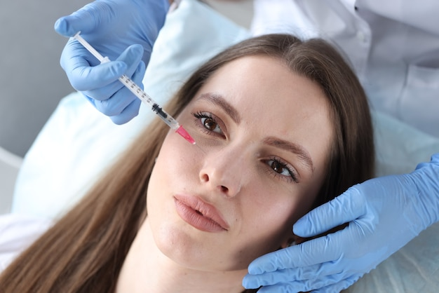 Young woman receiving antiaging injection in beauty clinic