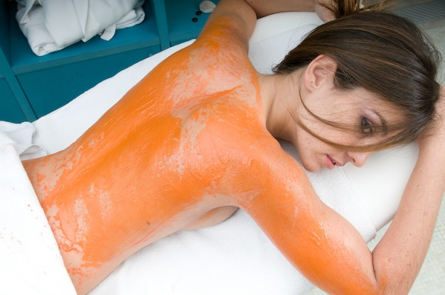 Young woman receiving a body treatment in a massage place