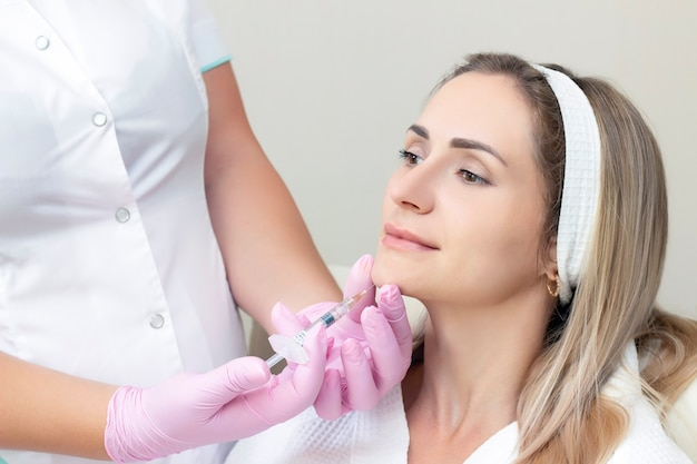 Young woman receiving cosmetic injection. woman in a beauty salon. plastic surgery clinic.