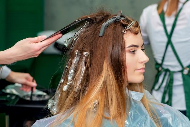 Молодая женщина получает окрашивание ее волос.