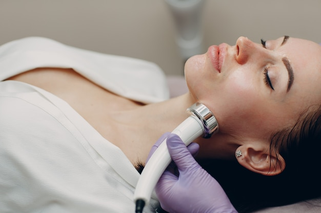 Young woman receiving electric rf lifting facial massage at beauty spa with electroporation equipment.