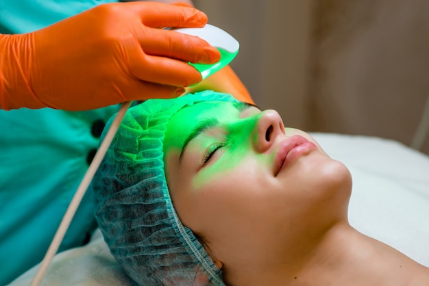 Young woman receiving epilation laser treatment on face at beauty center.