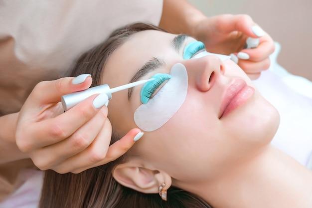 Молодая женщина, получающая процедуру ламинирования ресниц в салоне красоты, крупным планом