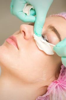 まつげの除去手順を受けている若い女性は、美容院で綿棒とスティックでマスカラを除去します。
