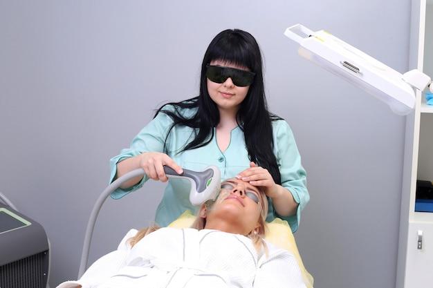 Молодая женщина, получающая косметические процедуры для лица, удаление пигментации в косметической клинике.