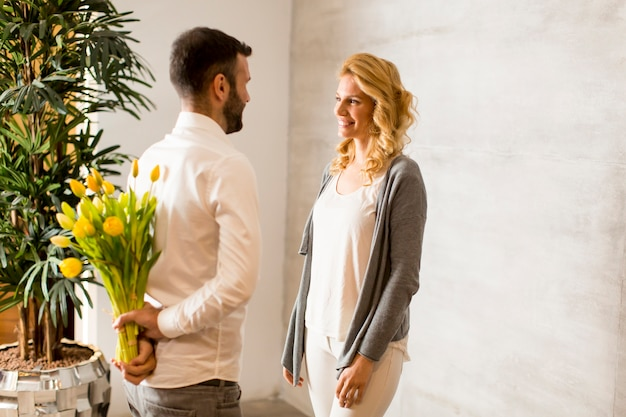 Young woman receiving a gift of yellow tulips from her husband or partner smiling at him