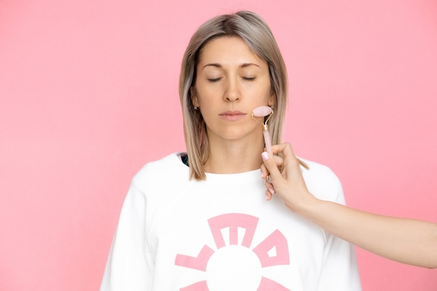 Young woman receiving gouache massage on pink background, studio shot, helping hand in spa, stock photo