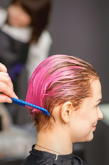 Young woman receiving hair treatment after pink coloring by hand of male hairdresser in hair salon