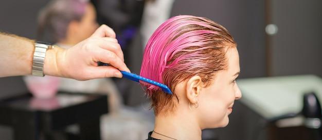 Молодая женщина получает лечение волос после розовой окраски вручную мужского парикмахера в парикмахерской