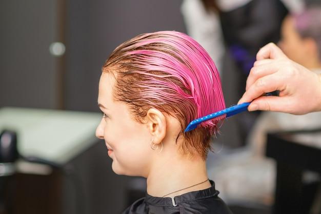 헤어 살롱에서 남성 미용사의 손으로 분홍색 착색 후 헤어 트리트먼트를받는 젊은 여성