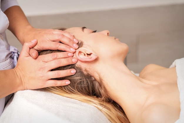 Young woman receiving head massage by hands of beautician in spa beauty center