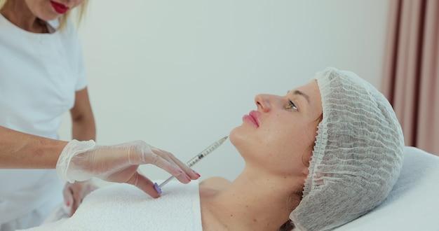 サロンでヒアルロン酸注射を受けている若い女性。若い美しい女性の唇の増強のプロセス。美容コンセプト。
