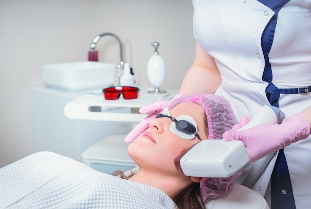 Young woman receiving laser treatment in cosmetology clinic. eyes covered with protection glasses