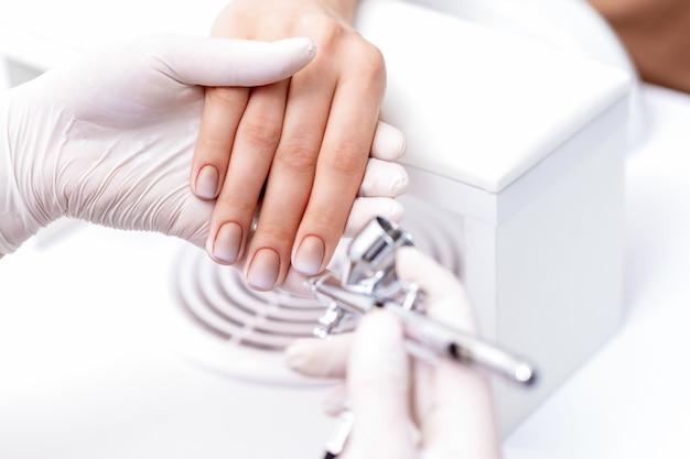 Молодая женщина, получающая маникюр с помощью аэрографа в маникюрном салоне. порядок нанесения краски на ногти