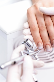 Young woman receiving manicure by airbrush in nail salon. procedure for spraying paint on the nails