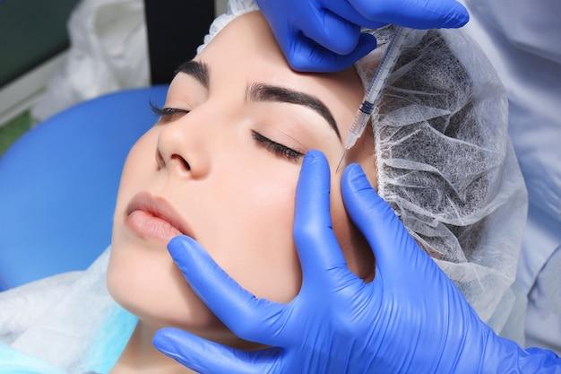 Молодая женщина получает инъекции пластической хирургии на ее лице, крупным планом