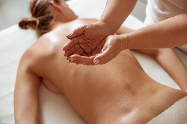 Молодая женщина, получающая профессиональный массаж в оздоровительном центре