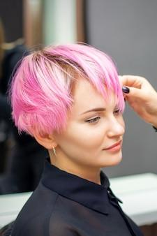 Молодая женщина получает короткую розовую прическу
