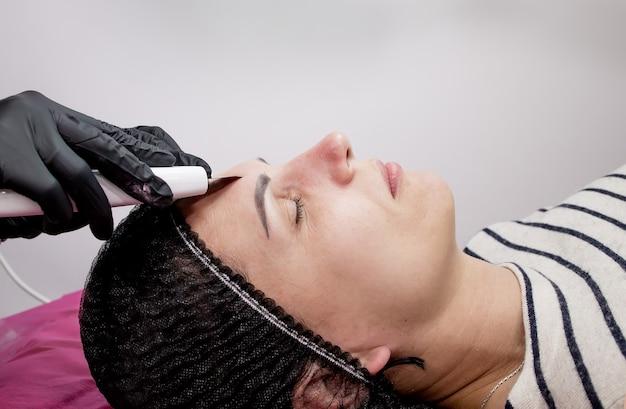 초음파 캐비테이션 페이셜 필링 클렌징을 받는 젊은 여성. 미용 페이셜 스킨 케어 트리트먼트 클리닝