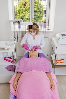 Young woman receiving ultrasound cavitation facial peeling cleansing. cosmetology facial skin care treatment cleaning.