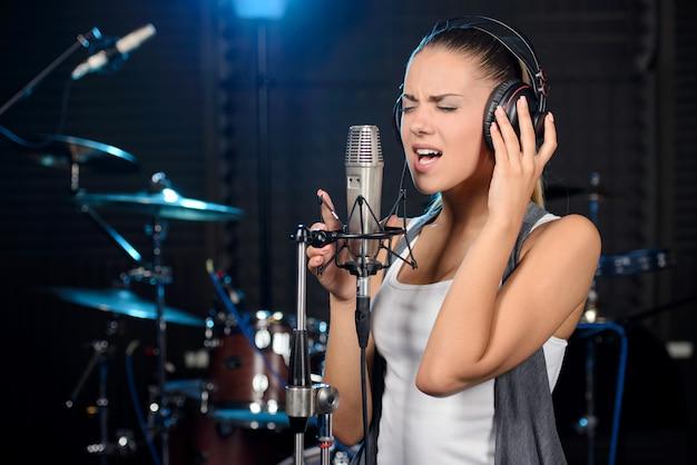 전문 스튜디오에서 노래를 녹음하는 젊은 여자