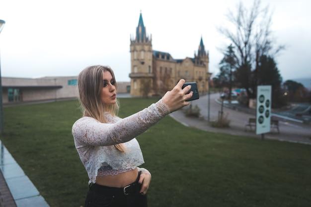 Молодая женщина записывает себя с мобильного телефона на улице.