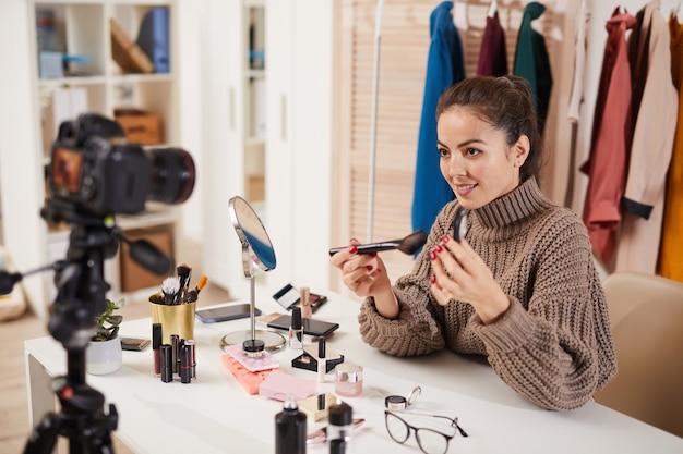 Young woman recording makeup tutorial
