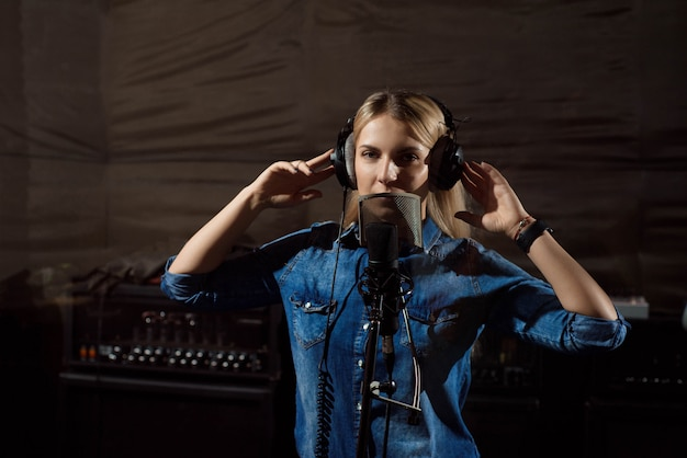Young woman in recording studio talking into microphone.