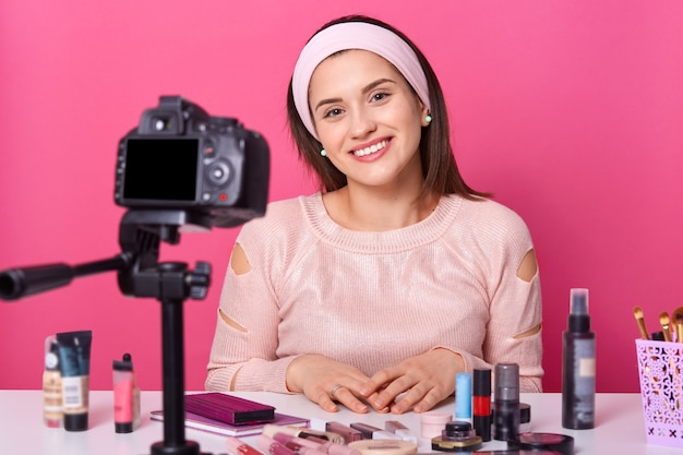 Young woman recording via camera on tripod for her vlog about cosmetics