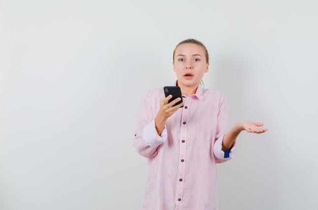 분홍색 셔츠에 휴대 전화에 음성 메시지를 녹음하고 혼란스러워하는 젊은 여자