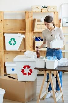 ガラスをリサイクルする若い女性彼女はゴミを別のゴミ箱に分類しました