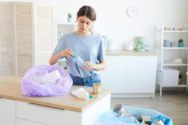 ペットボトルをリサイクルしている若い女性が、家庭の台所に立ってペットボトルをパケットに入れています。