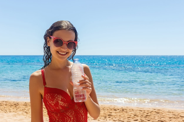 Young woman in a red bathing suit on the beach holding a bottle of water