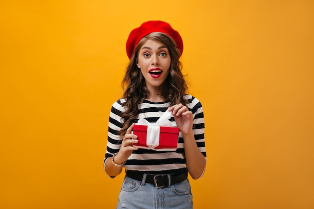 La giovane donna in berretto rosso e camicia a strisce tiene il contenitore di regalo. signora alla moda riccia con labbra luminose in gonna di jeans con cintura nera in posa.