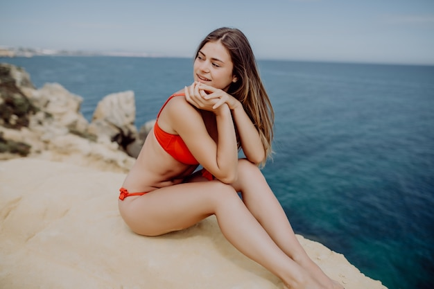 Young woman in red bikini with straight graceful legs sits on a stone near the sea water.