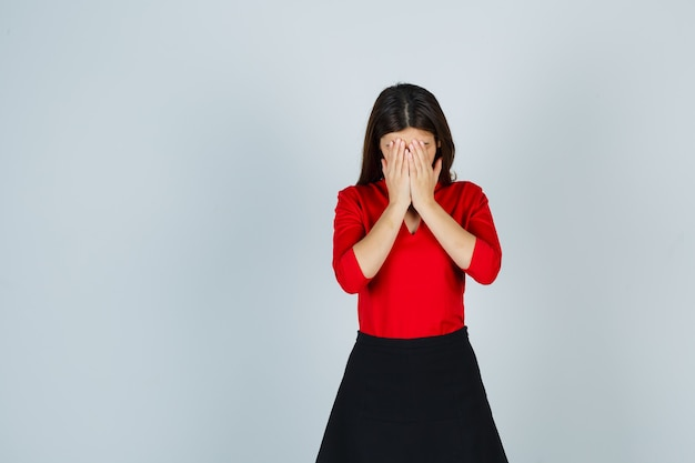 Giovane donna in camicetta rossa, gonna nera che copre il viso con le mani e sembra vergognosa