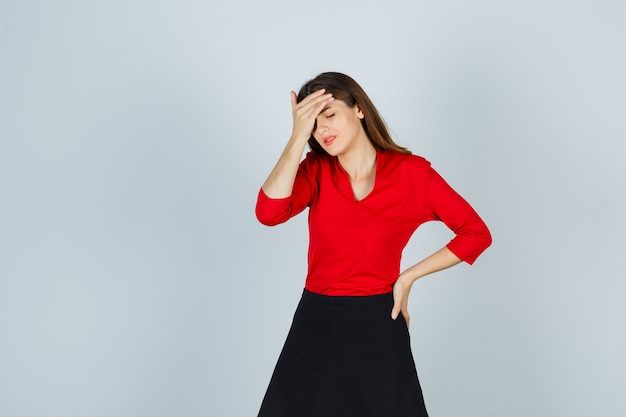 Young woman in red blouse, black skirt holding one hand on head