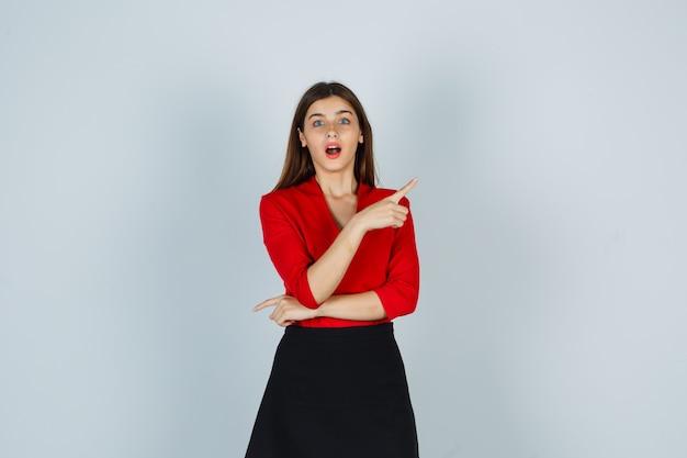 Giovane donna in camicetta rossa, gonna nera che punta a destra con il dito indice