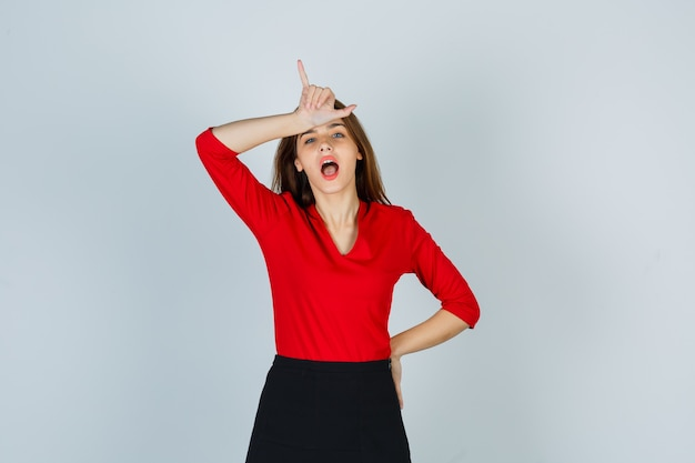 Young woman in red blouse, black skirt showing loser gesture
